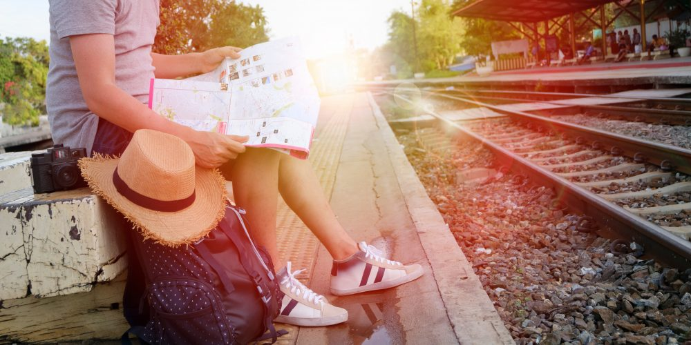 young man traveler with backpack and hat at the train station with a traveler , travel and recreation concept